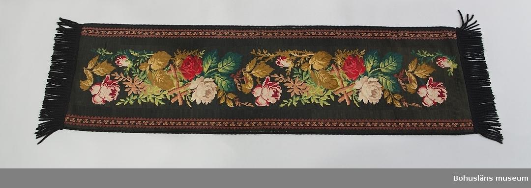 Fodrad, frans i båda ändar, foder och frans svart. Svart botten med rosenmönster i rött och vitt. Sliten på mitten.