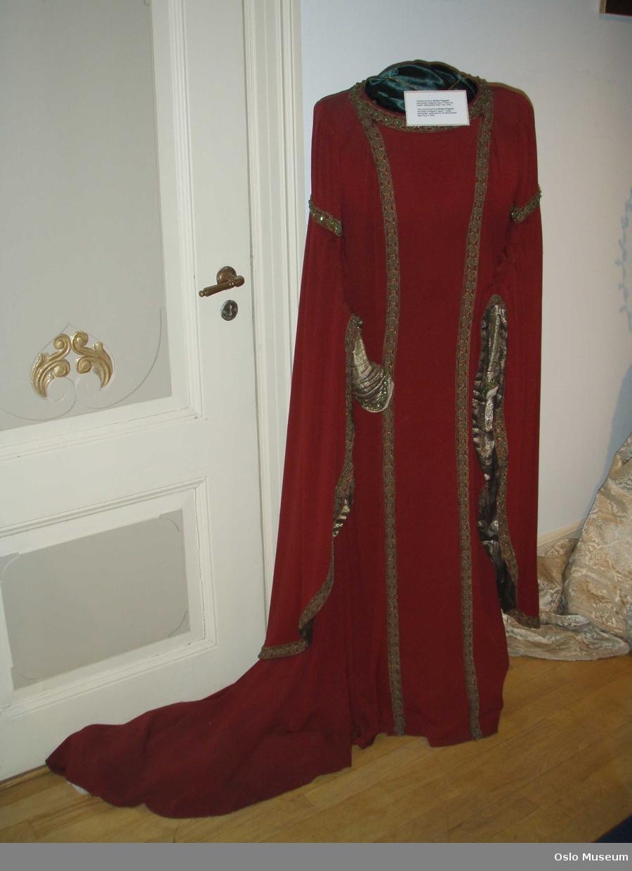 Fotsid kjole i rødt stoff med slep og vide ermer over trange underermer.Borderi i gull med grønne stener