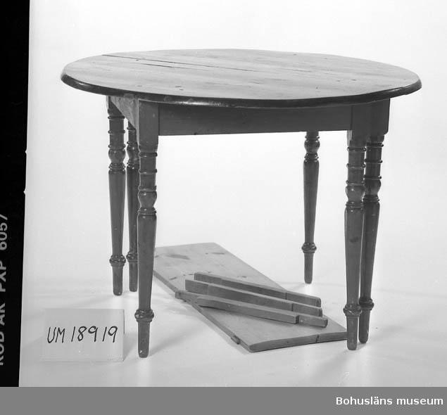 Runt bord med svarvade ben.Trä med mahogny fanér i skivan. Furu i  benen. Till bordet hör en separat skiva avsedd att placeras i mitten  för att utöka bordets yta. Fyra skruvar har skruvats i från skivan  ner i bordets underrede för att förstärka konstruktionen. Bordet + inläggsskiva = 6 delar.