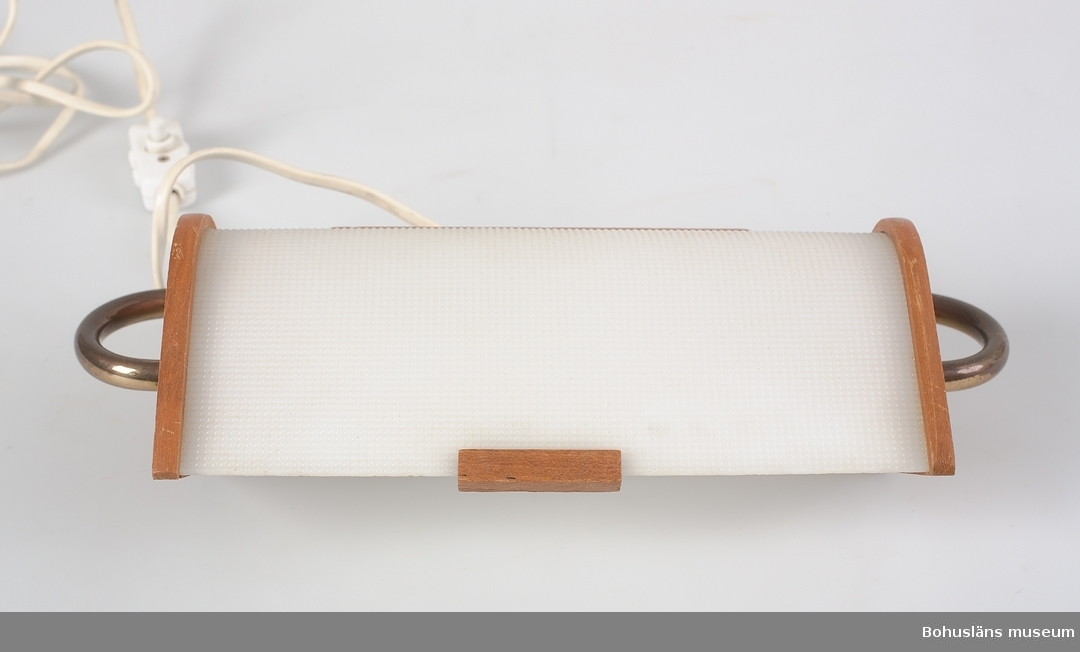Vägglampa (säng-) med skärm i vit plast, skärmen vridbar i höjdläge. Träplatta att fästa lampan på väggen i.