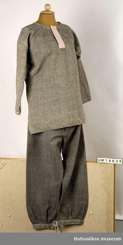 """Funktion: Underplagg för man. Mansskjorta i kypert med inslag av grått ullgarn och varp av vit bomull. Sydd av raka tygstycken och med kil under ärmen. Sprund i sidorna. Knäppt med en benknapp i halsen och på ärmarna. Halsen och sprundet förstärkt med röd och vitrandigt bomullstyg. Märkt: """"R.H."""" - broderat i kedjestygn med rött bomullsgarn under halssprundet. Lagad bl.a. på ryggen. Sliten och smutsig. Tröjan är kanske ett arv från brukarens far. Se liknande typ av plagg UM019801"""