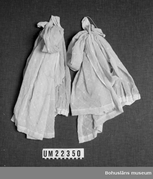 Tillhör UM022271. Tillverkad av mönstrat bomullstyg samt två omtag för upphängning.  UMFF 101:8