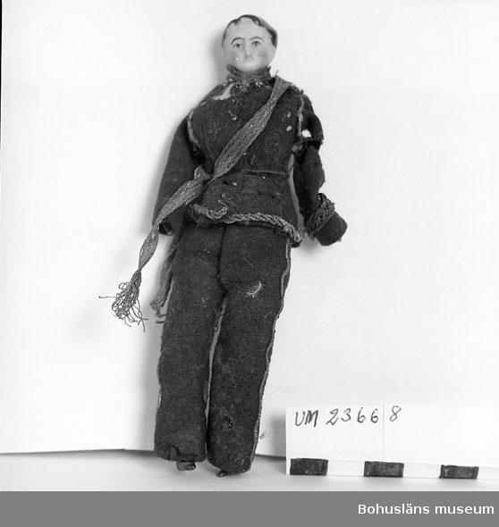 Föremålet visas i basutställningen Uddevalla genom tiderna, Bohusläns museum, Uddevalla.  Pojkdocka med tygkropp och underben och huvud i biskviporslin. Huvudet bemålat. Armar saknas. Klädd i ursprunglig uniform i blå vadmal med revärer och kanter av gul snodd. Rester av gehäng i guldtrådsliknande tyg. Jacka med skador, möjligen av mal. Dockans kropp är hemtillverkad.