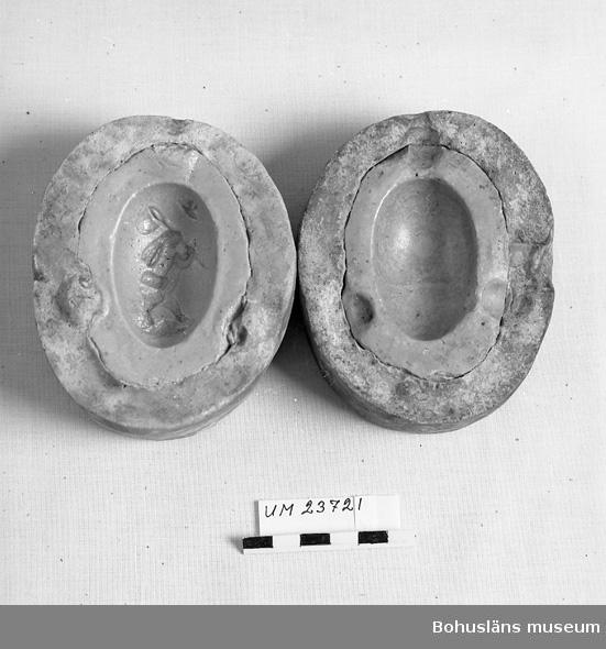 594 Landskap BOHUSLÄN  Oval i två delar. Ytterdelen av gips. Formdelen av konstmassa. Föreställer ägg. På ena halvan en figur.  Samlingen med formar från Svenssons konditori omfattar UM16775 - UM16897, övriga föremål  UM23716 - UM23736, UM23751 - UM23753.