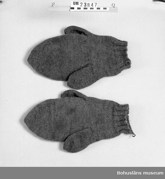 """Föremålet visas i basutställningen Kustland, Bohusläns museum, Uddevalla.  Vantar med två tummar. Bruna. En knapp vid mudden på den ena vanten  och en hank till knappen på den andra. Inuti vantarna är det linblånor. Det användes i äldre tid som medel mot ohyra. Lagningar. Gjorda av tillverkaren av egen kardad och spunnen ull samt med hennes eget röda hår. Tillverkaren bosatt med brukaren. Brukaren, född 1880 och död 1964, använde dem vid utomhusarbete hemma och på Bassholmen, där han arbetade under ca 30 år. Han rodde dit från Hjältön. Anledningen till att det är två tummar är att vanten skall kunna användas på två håll, kanske för att slitas jämnt eller för att kunna vändas om den blev mycket våt. Angående valet av material är det osäkert varför människohår använts. Det anses stå väl mot kyla och väta. Kanske togs hår från kärestan  för att fungera som skydd-/lyckobringare.  """"I Bohuslän har strumpor och vantar stickats med en blandning av ull och kvinnohår, vilket gav varma och vattenavstötande plagg. Med två tummar på varje vante kunde fiskaren vända på vanten när den blev våta på insidan under arbetet på sjön. Dessutom slets vanten runtom. Vantarna kunde ha en hank eller knapp som höll ihop paren, vilka hängdes på tork i kajutan. Ägarens initialer var instickade eller broderade i korsstygn. Hårvantarna användes i hela länet och de har stickats så sent som på 1970-talet. Det finns fortfarande fiskare som på 1990-talet inte går ut på sjön utan sina hårvantar. -Det är svårt att få tag på hår idag, berättade en gammal fiskare, vi fick hämta från en damfrisering med det är inte samma sak! Det var ju avklippt hår. När kvinnorna kammade sig sparade de löst hår från kammen i en burk och det kardades tillsammans med ull och spanns till stickgarn. Man kunde också ha löst hår i en korg och låta det följa garnet i stickningen. Unga flickor samlade sitt hår för att sticka sockor till den pojke de tyckte om.  Stickade sockor och vantar valkades för att bli varmare och mera sli"""