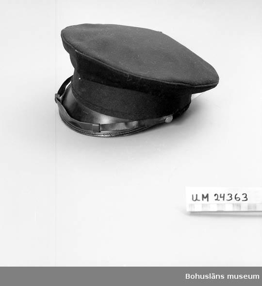 """106 OCM *743 594 Landskap BOHUSLÄN  Svart kulle. Svart skärm och ett hakband i något plastmaterial. Hakbandet sitter fast med metallknappar med kors och kungakrona. Hakbandet vilar mot skärmen. Hör till skötarnas vinteruniform. Har burits av Sigge Johansson. """"58"""" står tryckt inne i mössan. Ett märke förefaller ha suttit framtill på mössan, det finns rester av gulmetall."""