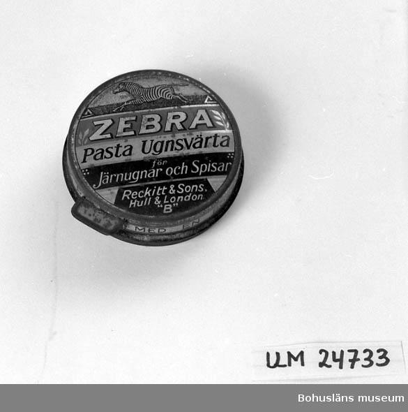 """471 Tillverkningstid 1920-1940?  Rund burk med lock i flera färger. Från locket går det ut en liten metallplatta  som skall vridas för att underlätta öppning av burken. Text uppe på locket:  """"ZEBRA Pasta Ugnsvärta för Järnugnar och Spisar Reckitt & Sons. Hull & London """"B"""""""" samt  """"INREGISTRERAT VARUMÄRKE"""". På lockets kant står det 2 ggr:  """"POLERA MED EN BORSTE"""". På locket är det en bild blå en zebra.  Locket går ej att ta av."""
