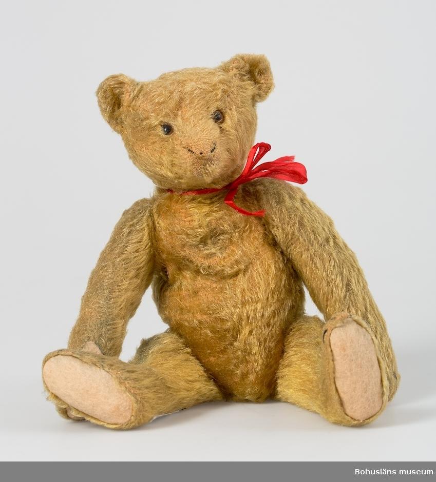 Leksaksnalle i gulbrun ylleplysch, ögon i brunt och svart glas, trampdyna av naturfärgat ylle. Rött sidenband kring halsen. Klor och tår markerade med svart tråd.