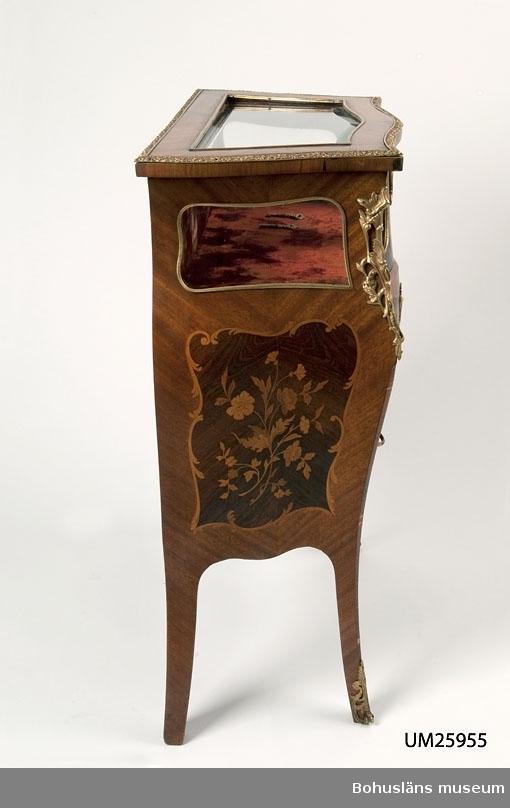 1900-talstillverkad byrå i rokokostil med två lådor och en övre vitrindel med glas på framsida och gavlar samt lock. Fyra ben. Handtag och hörnbeslag, lister och nyckelskyltar i mässing i rokokostil. Blindträ av ek. Fasad och gavlar med mahognyfanér med intarsia i olika träslag, även i rokokostil.  En nyckel till vitrinlocket och en till de båda lådorna.  Vitrindelen har innehållit minnes- och släktsaker huvudsakligen från släkterna Berg, Ekelund och Bark. Till denna föremålskrets hör UM16507, UM17080 - UM17081 och UM59.10.1.  Se också arkivmaterial i Bohusläns museum Enskilda arkiv; Barks arkiv.  Paul Berg f. 9 feb 1806 d 22 feb 1879, redare, handlare mm landstingsman, riksdagsman, stadsfullmäktiges ordf. Gift med Maria Josefina Berg f. Tidholm f 14 sept 1820, d 7 aug 1893. Dotter Pauline Berg g. Ekelund, f 1843 d 1881, gift med Frithiof Ekelund, f 30 sept 1838 d 30 dec 1915, överstelöjtnant, stadsfullm. ordf. Dottern Anna Ekelund g. Bark f 1880 d 1950, gift med bankdirektör John  Bark. Sonen Erik Bark, läroverksadjunkt f 24 april 1904 d 1990.  Litt: Kristiansson. Uddevalla stads historia, del III. Uddevalla 1956.