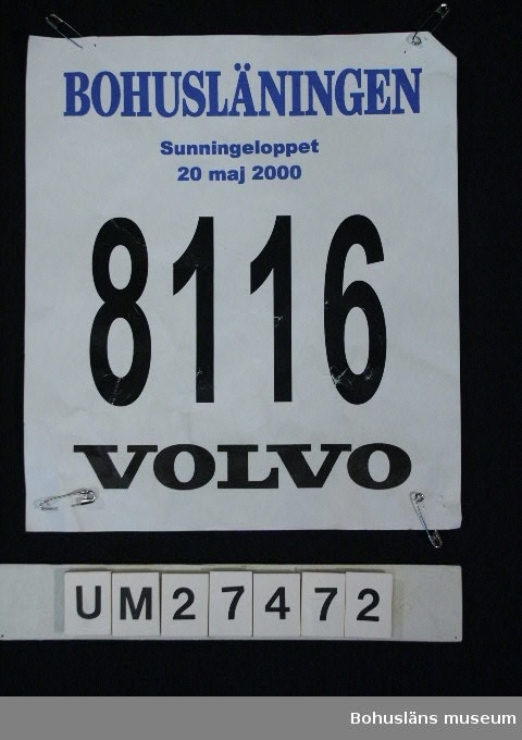 """Föremålet visas i basutställningen Uddevalla genom tiderna, Bohusläns museum, Uddevalla.  594 Landskap Bohuslän 501 Kön Kvinna  Nummerlapp av papper med fyra säkerhetsnålar och texten:  """"BOHUSLÄNINGEN Sunningeloppet 20 maj 2000""""  i blått,  """"8116 VOLVO""""  i svart. Nummerlappen har varit fäst på baksidan av T-shirt UM27470 med fyra säkerhetsnålar.  Nummerlappen har använts vid invigningen av Uddevallabron i Uddevalla kommun den 20 maj 2000 på det s k Sunningeloppet, en löptävling med 7300 deltagare i alla åldrar med Oddevold som arrangör. Man kunde välja mellan fyra olika distanser; en """"halvmara"""" om knappt 21 kilometer, ett """"millopp"""" på 10,7 kilmoeter, en fyrakilometers-bana och ett """"knattelopp"""" om två kilometer. Varje tävlande bar en T-shirt med nummerlapp och erhölll  efteråt  en medalj.har använts vid invigningen av Sunningebron i Uddevalla kommun den 20 maj 2000 på det s k Sunningeloppet, en löptävlingVarje tävlande bar en T-shirt med nummerlapp och efteråt erhöll en medalj.  Litt: Sunningeleden. Den vackraste genvägen. Uddevallabron. Red. Viveka Overland, Uddevalla 2000, s. 136 - 145."""