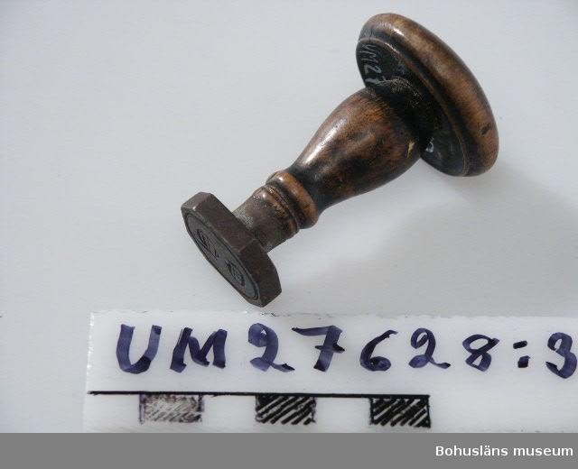 """Uppgifter om Mått  och Brukare avser de två största stämplarna.  Tre ovala stämplar för lack eller stämpeldyna av gjuten mässing med text i nedsänkt relief. Handtag av svarvade träknoppar, märkta UM27768:1: """"A. C. O."""" inom oval ram,  (Anna Christina Olsson), UM27768:2: """"A. C. Olsson"""" inom oval ram samt UM27768:3 """"CL"""" i frakturstil inom oval ram (Christian Lachonius).  För uppgifter om personerna  samt använding inom handelshuset på Härön, se UM27621."""