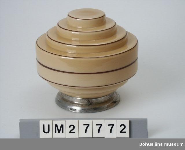 """Taklampa för elektriskt ljus. Sockel av förnicklad aluminium med lamphållare av mässing märkt """"ZENITH"""" för normalstor glödlampa. Sockeln fästad i lampglaset med tre monterbara skruvar. Lampglas av svagt bruntonat glas med bruna kantränder i 1930-talets populära modernistiska formade """"rymd- eller planetform"""" i sex våningsplan.  Se uppgifter under Övrig information (intern)."""