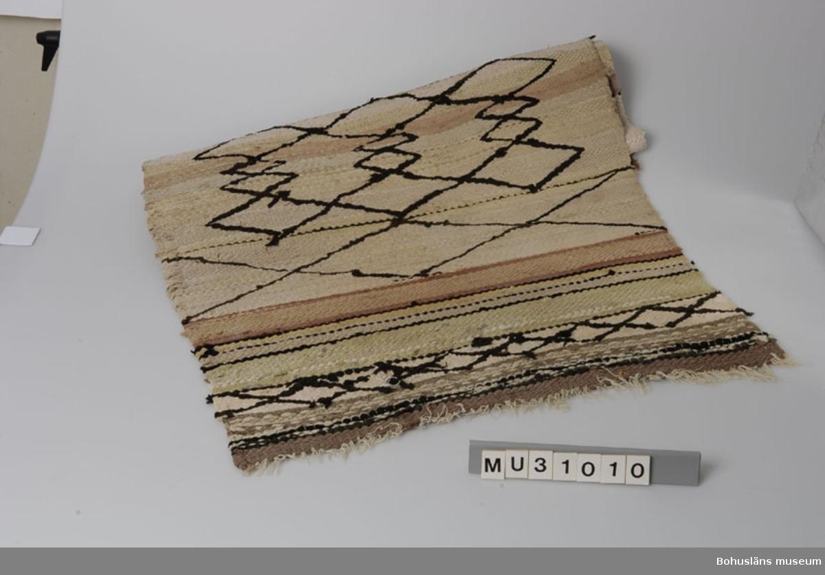 """Matta, ensidig, med bomullsvarp och med inslag av pastellfärgade bomullstrasor av trikå i rosa, grönt, vitt och beige. Omväxlande breda och smala ränder. Dekor av bruna rombiska former inplockade över hela mattan (slarvtjäll).  Relativt sliten. Delvis trasiga kanter.  Trasmattan är tillverkad av Gunhild Andrea Arvidsson (1894 - 1981), Gullholmen 5.13, syssling  till Karin, som skänkte det föräldrahem som gjordes till museum, Skepparmuseet på Gullholmen.    Hon  var ogift och gick som ung något år på Tyft folkhögskola på 1920-talet. Hon arbetade något i konserven men var annars mest hemmavid. """"Arvidssons behövde inte arbeta"""".   Även sysslingen Anna  tillverkade folkdräktsliknande plagg som hon ibland komponerat själv. Dessa kan ses på skyltdockor på museet på Gullholmen.  Systrarna hade också del i gård på Hermanö, """"gårdslott"""", vars lagård idag är Gullholmens konstmuseum. I 60-årsåldern byggde Andrea en sommarstuga på Hermanö, """"Solbacken"""",  vilket alla tyckte var konstigt. Hon vågade dock aldrig övernatta där """"eftersom hon var synsk"""".   En gång gjorde hon illa  benet och då hämtade givarens far (jordbrukare på Hermanö) henne i traktorkärran och tog henne hem till """"vinterhemmet"""" , det gula huset alldeles intill affären. På detta sätt skjutsade han henne sedan under flera år. Hon vävde fram till 1960-talet.  Se uppgifter under Ort. Litt: Lychou, K.: Folkkonst i Bohuslän, Warne förlag 1996, s. 104 ff."""