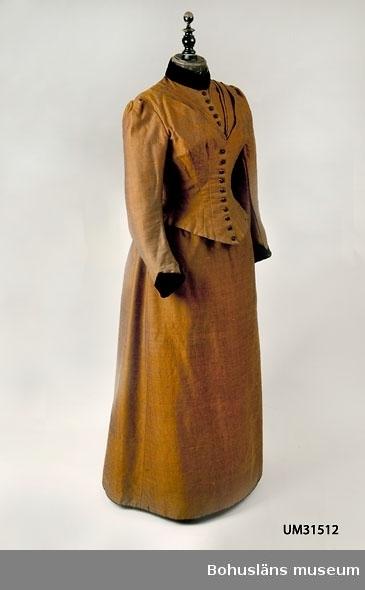 Kjol till klänning i två delar sydd av vävt brunt skimrande ylletyg i kypert. Varpen består av ett kardat blått ullgarn och inslaget är ett kamgarn i en ljusare gulrödbrun nyans. (Se UM031512 Klänningsliv). Hellång kjol, längre bak. Framtill med en våd, tre våder samlade baktill, rynkade mot en smal dubbelvikt linning. Kjolen mäter 248 cm omkrets nedtill. Nederkanten skodd på insidan med ett 23 cm brett  brunt linnefoder. Svart ripsband påsytt som slitkant runt nederfållen. Knäppes baktill med två hakar och hyskor fastsydda i linningen. Hakarna saknas. De är ersatta med två nyisydda av försilvrad mässing tillverkade av Gusum, en mindre storlek. Hyskorna är av järn.
