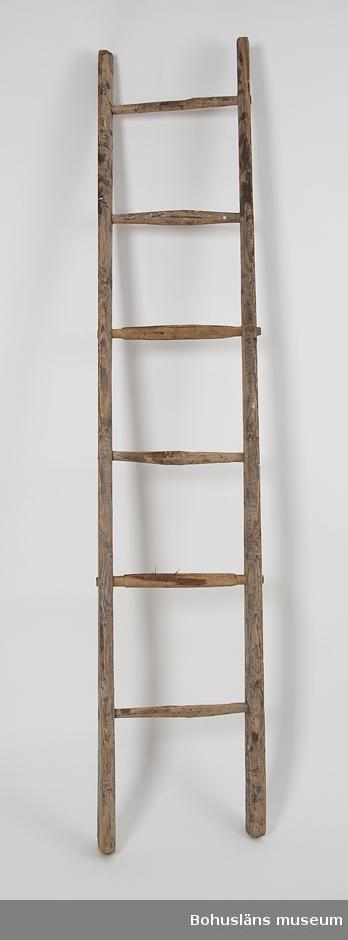 """Trästege med sex itappade fotsteg. Långsidorna  tillverkade av en itusågad trästam, fotstegen är handskurna. Hela stegen är något vriden. Färgrester. Båtbyggaren Viktor Löfberg (1878-1962) grundade 1919 ett båtvarv i Rönnäng. Varvet drevs vidare av sonen Tore (1915-1979 under namnet V. T. Löfbergs slip- och båtvarv och övertogs därefter av sonsonen Tomas, f. 1948.   Materialet från insamlingen transporterades till Bohusläns museum i september 2011 i samband med att varvets byggnader skulle rivas.  Se också foton under UMFA55080; Varvsägaren och båtbyggaren Viktor Löfberg (1878-1962) med sonen Tore (1915-1979) och sonsonen Tomas, f. 1948, utanför Viktor Löfbergs hus i Rönnäng, ca 1950.  Litt. Ohlén, B. """"Fiskebåtsvarv i Bohuslän - industrihistorisk dokumentation av Hälleviksstrands varv, Rönnängs varv, Studseröds varv"""". Bohusläns museum. Rapport 1999:43."""