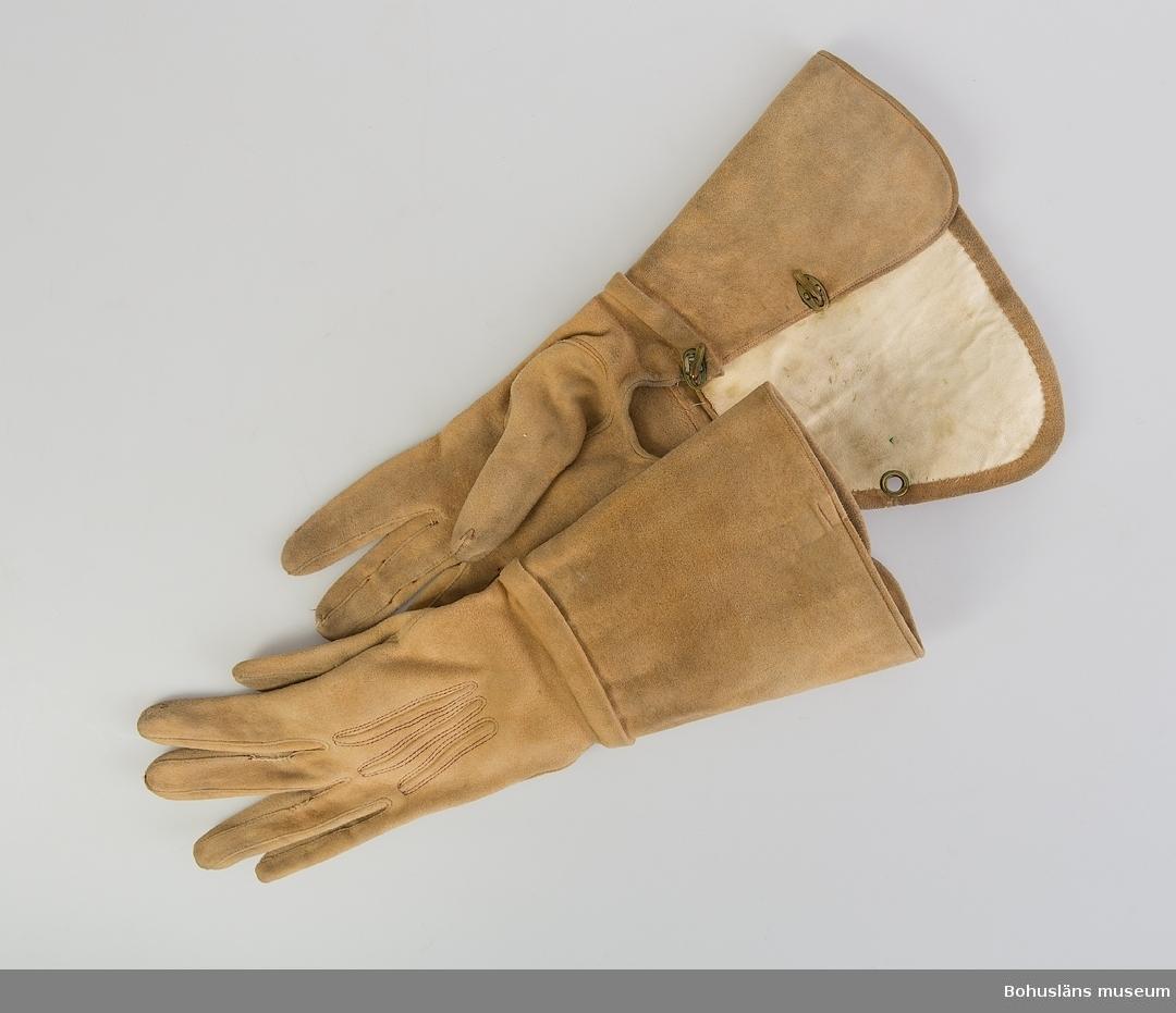 Ljusbruna handskar med ca 12 cm lång krage. Av sämskskinnsgarvat skinn (från och med ny beredningsmetod på 1920-talet kallat mocka.) På handens ovansida finns tre laskningar och dekorstickningar med rödbrun tråd runt dem. Kragen fodrad med vitt skinn. En kombination av maskin- och handsömnad. Kragen fästs samman med uppfällbara mässingshakar som träs in i hål med öljetter (en öljett saknas på högerhandske, delvis ersatt av sydd ögla). Sömmen mellan högerhanskens handdel och krage till stora delar borta. Lagning med kaststygn finns. Samma vante saknar en öljett - se ovan. Vänster handske saknar en mässingshake. Båda handskarna har lagningar på fingrarna och är något smutsiga. De är märkta med blått bläck U.M.62.4.6 a respektive U.M.62.4.6 b  Del av riddräkt UM62.04.001 - UM62.04.007 Mer information se UM62.04.001