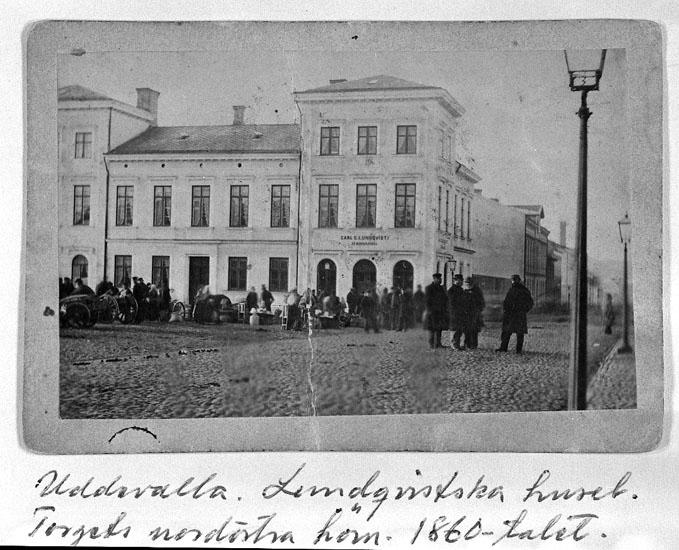 """Text på kortet: """"Uddevalla. Lundqvistska huset. Torgets nordöstra hörn. 1860-talet"""".  Enligt tidigare noteringar: """"Lundqvistska huset, Torgets nordöstra hörn. 1860-talet.  Repro 1984 av foto""""."""