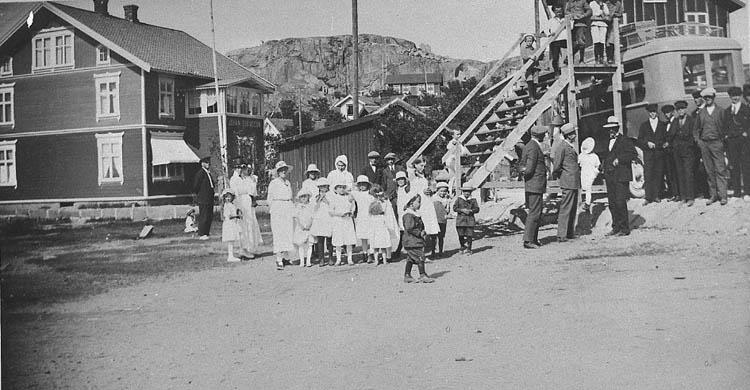 """Enl. tidigare noteringar: """"Busstationen i Bovallstrand. Bland folket på bilden flera finklädda barn. Ställning med trappa för lastning på busstak.  Repro 1985 av foto tillhörande Gustav Rundberg, Bovallstrand""""."""