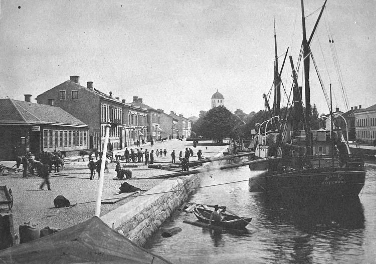 """Enligt notering: """"Lossning av aspstockar till tändsticksfabriken. SS Magne Göteborg i Bäveån ca 1890""""."""