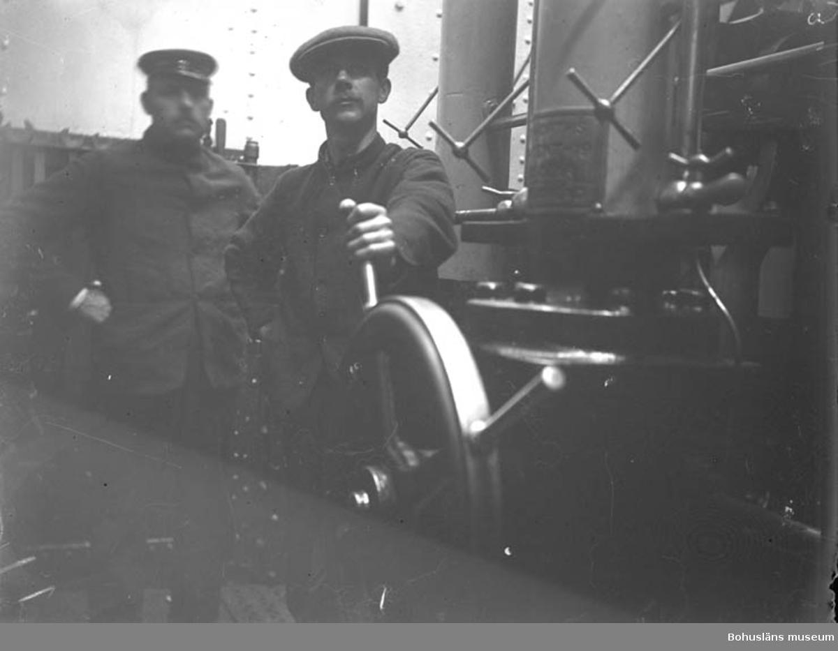 """Text till bilden: """"Kapten och sjöman vid rodret""""."""