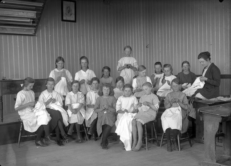 """Enligt fotografens noteringar: """"Elin Sahlberg med syelever- Håby. Elin Sahlberg slöjdlärarinna i Håby socken. Omkring å 1925."""""""