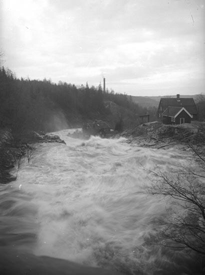 """Enligt fotografens noteringar: """"Öfversvämning omkring å gamla bruket. Arbetarbostad vid Munkedalsälven."""""""