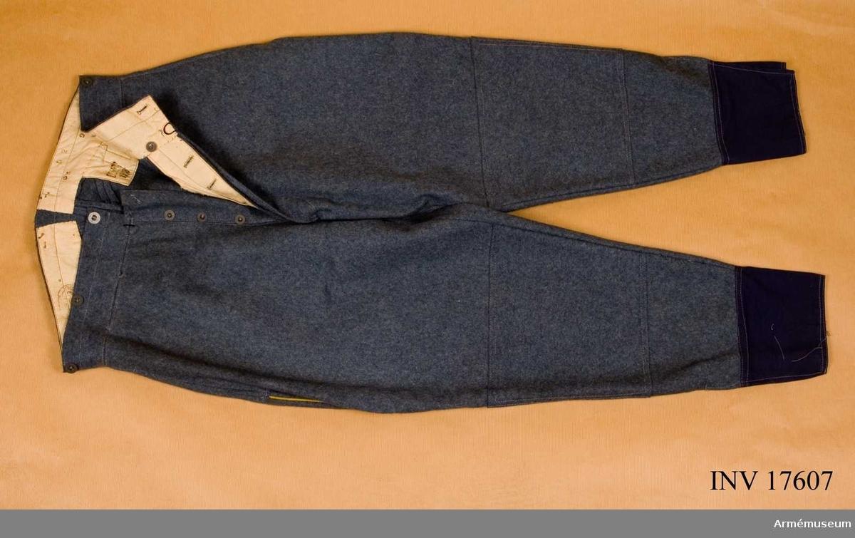 """Grupp C II. Byxor av gråblått (horisonntblått) kläde med två fickor på sidorna och sprund med fem järnknappar, sex knappar för hängslen, hyska och hake. Foder av vitt tyg med stämplar: """"Commission de réception 1918"""". På byxornas baksida spänntamp med spännen. Nederst på byxbenen finns ett 12 cm brett uppslag av blått bomullstyg, försett med sprund. Vid knäna en likartad remsa 22 cm bred (knäförstärkning) som är fastsydd vid byxbenen. På sidorna finns gul passpoal av kläde. Litteratur: Handbuch der Uniformenkunde, prof R. Knötel, Hamburg 1937 sid 161. Efter stora förluster i krigets början infördes år 1915 vid franska armén i stället för den gamla fredsuniformen en ny av gråblått kläde (horisontblå färg). Byxorna är försedda med gul passpoal på sidorna. Enligt kapten W. Granberg."""