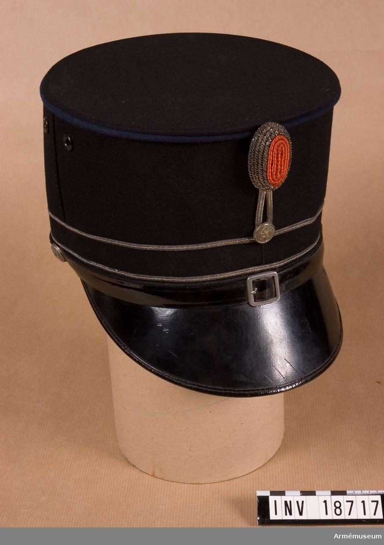 """Grupp C I. Uniform m/1866 för officer, premiärlöjtnant, vid 1., 2., eller 4. Husarreg:a, Blå kavalleriet, Holland. Käppi klädd runt omkring och i botten med mörkblått kläde. Skärm av svart läder. Runt omkring övre kanten har den en passpoal av blått kläde och på nedre delen två passpoaler av silversnören. Foder av rött tyg med firmananmn : """"A. Hassing"""" med holländska statsvapnet ovanför """"Amersfoort"""". Runt käppin inuti en  svettrem av gulläder. Hakremmar med järn spänne av svart läder, knäppes till käppin med knappar av vitmetall med holländska statsvapnet (lejon), d:140 mm. Kokarden på käppins framsida sitter vid övre kanten och är dels holländska nationalkokarden för officerare, i oval form. rött silke i mitten och vita silversnören runt omkring och  dels en knapp av vit metall med statliga nationalvapnet  (lejon) d:140 mm. Mellan dessa två kokarder finns två vita vita bommullssnören. På käppins båda sidor två luftventiler av  järn. LITT  Handbuch der Uniformkunde. Prof Richard Knötel, Hamburg 1937. Sida 253. År 1867 infördes för kavallerireg:a husaruni- formen av mörkblått kläde. Arméen Album II. Die Niederländische Armee, J. Hohman, Leipzig. Verlag von Moritz  Ruhl. sid 15 : Husaren. Officerarna använda """"Dienet"""" käppi med silversnören. Beschrijving von de Uniformen von de Nederlandische Lantmacht, De Geroeders von Cleaf 1900. sida 95. Kepi. Fullständig beskrivning på käppi på holländska.Enl kapten W Granberg 1954."""