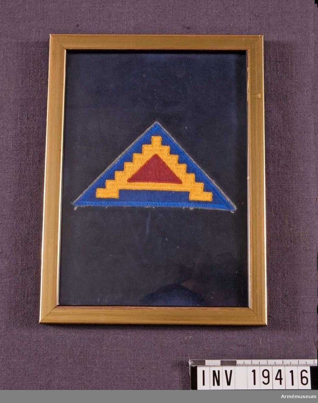 """Maskinbroderat märke i blått och gult och har form av en triangel. Motivet består av tre trianglar längst in i en röd och därefter en gul trappstegsformad triangel och ytterst en blå. Detta märke är inglasat i en guldram med text på baksidan: """"Här ett litet minne av vår tids historia. Med hopp om mitt bidrag `The Fighting Lady o Lady be Good' håller ämnet HISTORIA levande."""