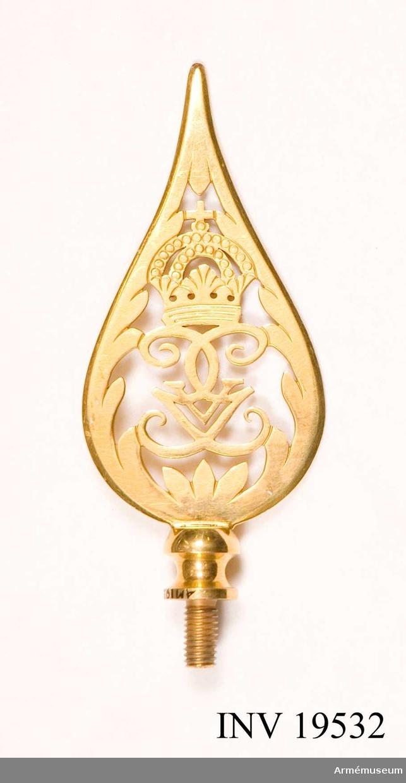 Fanspets, Gustav V:s monogram. Spetsen är tillverkad av förgylld mässing. Den har Gustav V:s spegelmonogram under en kunglig krona inramat av ett bladverk som avslutas i en smal spets. Spetsen är försedd med skruv. Spetsen till hör fana AM 19531.    Samhörande nr AM 19531-19534, fana, spets, kravatt, fodral.