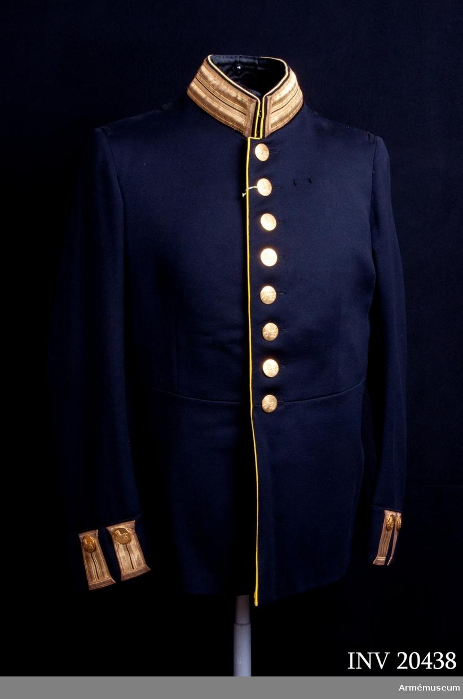 """Grupp C I. Ur uniformering för officer Hallands regemente I 16. Består av vapenrockar, långbyxor, kappor, mössor, päls, handskar, ridstövlar. Av mörkblått, ev. svart, diagonaltyg. Knappar guld. Gul passpoal runt krage. Axelklaff i guld.  """"Mattor"""" på krage och ärmuppslag, guld.  Anm. """"Paraden"""", dvs plåt och plym för mössan (inf) och epåletter (i st. f. axelklaffar) försvann 1932-01-01. Därefter är stor högtidsdräkt m/ä: vapenrock med axelklaffar, skärp m/1819, långbyxor med hällor, resårkängor, vita handskar. Buren av givarinnans make Uno Lindberg."""