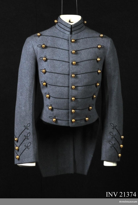 """Grupp C I. Ur uniform för kadett i West Point, USA. Består av frack, långbyxor, kappa, skärmmössa, tschakå med ståndare, tygfodral, vantar, livrem, fältmössa. Av grått kläde. På bröstet, längs detsamma, 3 rader knappar med 8 knappar i varje rad, tvärs över bröstet 8 svarta smala dubbelsnören, bildande vid yttre knappraderna, av samma snöre, 3 öglor mellan varje knapp. Samma beläggningar av snören finns på kragen, ärmuppslag och skörten. Foder av vitt bomullstyg. På ryggen finns fastsydd lapp av vitt tyg med påskriften: """"No 7755. Wata 7-10-37 (1937) Cadet-Store, West Point, Name Gillespie R. A. 18 I 19 2 36. 30.38-17, 32 2, 2, 15 3"""". Maker oläsligt. Krage, stånd, rakskuren, av samma kläde, kantad med svarta snören, på övre och nedre kanten. I mitten två svarta snören med 3 öglor mellan knapp (på kragens båda  sidor). Kragen har foder av samma kläde och 3 hyskor och hakar av vit metall för att fästa vid kragen, på vilken finns påskrift """"Gillespie R. A. West Point 15 (en halv)"""". Knappar, kullriga, guldfärgade,1,5 cm i diam, det finns 24 st på bröstet 12 st på skörten och 6 st på varje ärmuppslag. Skörten har slits 36 cm lång, vid slitsen finns 3 rader knappar, 2 st i  rad. De översta två knapparna i midjan. Ärmupplag, på ärmarna finns beläggningar av svarta snören 3 på varje ärmuppslag. i vinkelform med 1 knapp i mitten och med 3 öglor vid yttre rader LITT  Soldiers of the American Army 1775-1941, Drawings by Fritz Kredel, H. Bittner and Company, New York 1941. Plate 7 """"U.S. Military Academy 1925"""". På denna bild finns kadett i paraduniform i samma frack som denne, med samma knapprader, snören på bröstet, skörten och ärmuppslag. USA Militärakademi grundat år 1802 och i år 1825 hade Akademien redan 250 kadetter Die Armee der Vereinigten Staaten vom Amerika. Von de witt  Clinton Falls. Verlag von Moritz Ruhl, Leipzig, sid 15. """"Das  militärische Erziehungs und Unterrichtswesen"""". Kort beskrivning om Militärakademien i Weast Point. Bilaga: bild i färger, sid 5 olika kadettun"""
