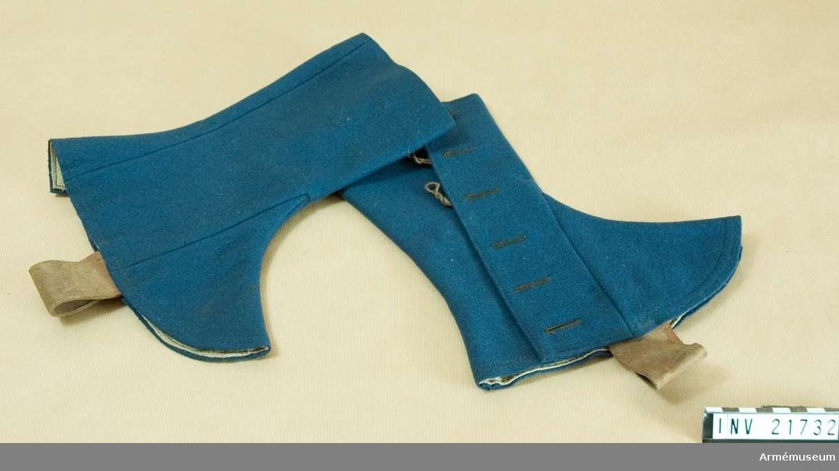 """Grupp C I. Av blått kläde. Knäppes på sidan med 6 svarta järnknappar; 3 knappar på övre delen knäppas med läderöglor för att sätta fast över byxorna och 3 nedre med endast knapphål. Hällor av brunt läder och fodrade med grov linnelärft som har stämplar; på V damask """"71 C"""" = Infan.Reg. Galgötz Nr 71, och på den H """"Q B & C"""" =någon firma, """"2"""" =storlek. Pappersetikett med text """"Tillh.Regte Gyllensvärd-Reserapport 1892"""", """"Österrike. Damasken m/88."""", """"Vigt. 0,19-0,21 kg"""". På andra sidan """"Generalintendentens expedition""""."""