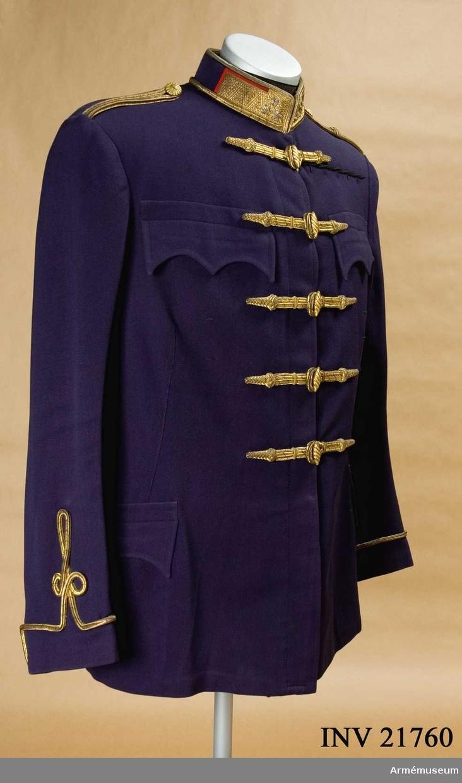 """Grupp C I. För överste vid 14:e Husarregementet, Österrike-Ungern. Blusen av mörkblått kläde. Enradig med 6 st svarta benknappar som knäppes innanför och 5 st knappar i oval form av gulmetall. Tvärs över bröstet finns 5 rader beläggningar, l:100 mm, på båda sidor, av dubbla grövre fyrkantsnören av guldsilke med broderingar på ändarna och knapphål. Axeltränsar på båda axlarna i form av dubbla fyrkantsnören av guldsilke, en knapp på varje axelklaff. På V träns finns löpare broderad av guldsilke. Fickor, två i rocken sydda sid- fickor och två bröstdito, alla med 3-uddiga ficklock. Knappar på blusens framsida:svarta benknappar, d:15 mm, 6 st, och 1 st med d:20 mm, avlånga i oval form av gulmetall 5 st husarknappar, på axeltränsar en på varje, d:20 mm, runda av gulmetall, husarknappar. Krage av samma kläde, upprättstående, med raka vinklar. Fyrkantssnören av guldsilke på kragens övre och nedre kant och framtill. På kragens båda sidor klaffar av krapprött kläde =känneteckensfärg för 14:e Husarreg:t, med zig-zag guldgalon och 3 stjärnor broderade i silver. Galon =kännetecken för regementets officerare (i österrikiska armén -""""Stabsoffiziere"""") 3 stjärnor kännetecken för överste. Ärmuppslag, på ärmarnas nedre kant beläggningar av grövre fyr- kantsnören av guldsilke, runt omkring ärmar och tre öglor (en stor). LITT  Armeen Album III. Uniformen und Abzeichen der Österriche- Ungar. Wehrmacht. K.K. Oberst M. Judex. Moritz Ruhl. Leipzig 1908. Sida 16. """"Regiments-Unterscheidungs-Zeichen"""". """"Krapprot- egalisirung"""", """"gelbeknöpfe"""", """"Regiment Nr 14"""". Adjustirungs und Ausrüstungs-Vorschrift für das K.K. Heer. Wien 1871. Sida 264: """"Blouse"""". Sida 262: """"Die Oliven (husarknappar) - beskrivning. Sida 240: """"Blouse"""" för dragonofficer. Sida 107: Blouse"""". Sida 106, 107: """"Distinctionen"""" - kännetecken för överste: galon för regementsofficerare och 3 silverstjärnor. Sida 31: """"Blouse"""" med 4 fickor och 6 knappae - beskrivning och bild.Handbuch der Uniformkunde, Prof. Richard Knötel. Hamburg 1937. Sida"""