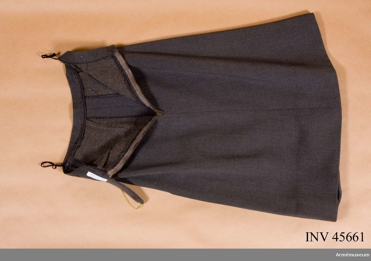 Grupp C I.  Ur kvinnlig tjänstedräkt m/1942 för korpral vid Stockholms  kvinnliga bilkår (del av Sveriges kvinnliga bilkårers  riksförbund?).  Består av jacka, kjol, blus, slips, mössa.Till uniformen bärs bruna skor och beige strumpor. 2 vinklar på ärmen = korpral  Märke på ärmen = uppkörning med lastbil  Föreningsmärke över högra fickan = föreningsmärke  Förtjänsttecken över vänstra fickan.  Samhörande nr är AM.045660-4, uniformspersedlar.