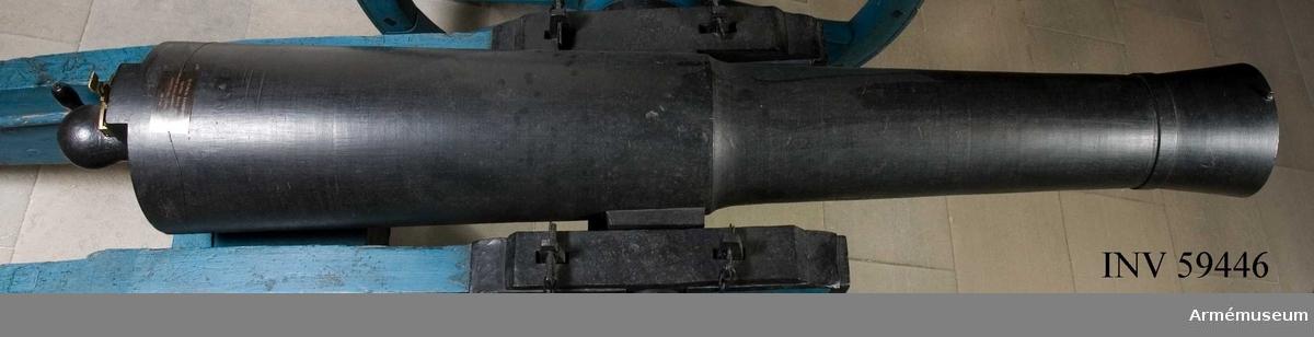 """Grupp F I.  ELDRÖR, längd: 2000 mm. BOTTENSTYCKE Max. diameter: 355 mm. TAPPSTYCKE Min. diameter: 290 mm. Tappskivans läge: 805 mm. Tappläge I: 835 mm. Tapp, längd: 105-110 mm, diameter: 105 mm. LÅNGA FÄLTET Max. diameter: 255 mm. Min. diameter: 210 mm. Främre frisläge: 990 mm. Halsband, läge: 1780 mm, bredd: 35 mm. Trumfens max. diameter: 255 mm. Tapparna under kärnlinjen med tappskiva. Tappskivans läge: 805 mm. Form och placering - se bilaga. Tapp vänster har årtalet 1808 och tapp höger är märkt """"ÅB"""" i ligatur, allt med upphöjda, rundkullriga siffror och bokstäver. Trumpetförstärkt trumf. Loppet vidgar sig trumpetformigt. """"Kalibern"""" i själva mynningen är 16,8 cm. Kanonens övre parti skjuter baktill ut en smula för siktin-  rättningens fästande.  Druvan är spetskulformig. Inristning på dess fot: """"29"""" och """"2,5"""". Fängpanna saknas; fänghål - se bilaga. Sirater, friser och band saknas utom bakbandet. Dessutom bildas på framfrisens plats en gräns, genom att kanonens tjocklek härifrån kraftigt minskas.  Kanonen är sammansatt av eldrör, lavett, riktskruv med vev, pinnkapell, handspik, inventionsviskare med borste, fodral till viskarehuvud, plunderskruv, föreställare med tistel och två svänglar, luntstake med lunta."""