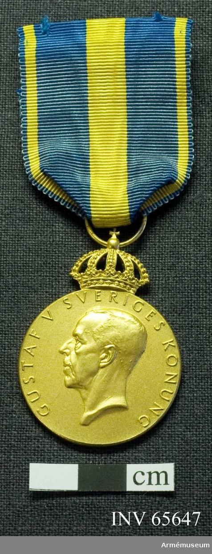 """Grupp M II. Åtsidan har kung Gustav V i vänsterprofil angiven av """"GUSTAF V SVERIGES KONUNG"""". Grånsidan har """"KUNGLIGA AUTOMOBIL KLUBBEN +"""" utmed kanten. Kontroll- och tillverkarstämplar """"S & Co (Sporrong) vid nederkanten. En kunglig krona på medaljens överkant. Bandet är blått med gula kanter och en bred, gul rand på mitten. Fästnål saknas."""