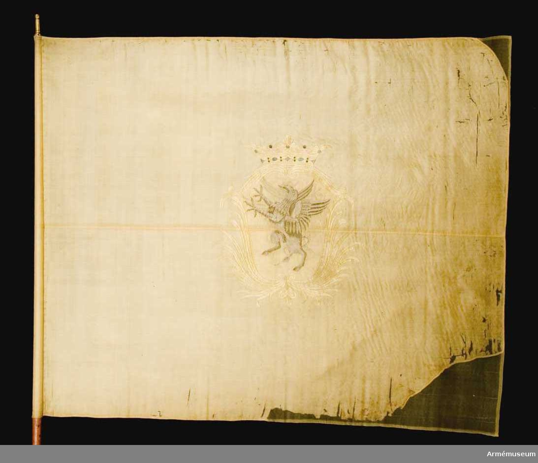 Duk: Tillverkad av enkel citrongul sidentaft. Två våder sammansydda horisontellt. Kantad med ett mönstervävt band. Fäst med en rad tennlickor på samma band som duken kantas med.  Dekor: Broderad lika på båda sidor, i mitten Södermanlands vapen, en grip i grått silke, schattersöm, på gult fält i en av stiliserade palmkvistar bildad sköld i gult silke, krönt med öppen krona i gult silke, pärlor i silver. Broderad plattsöm.  Stång: Omålad, av trä. Avsågad. Holk av förgylld mässing.