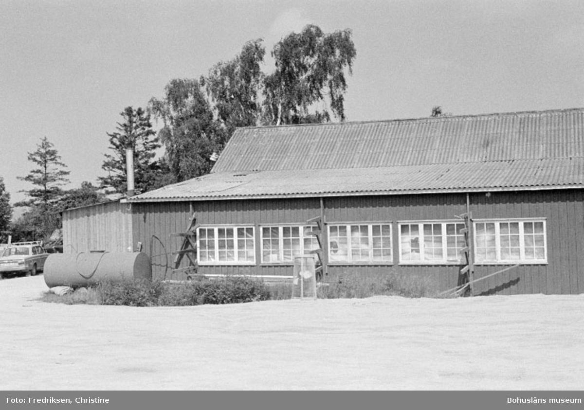 """Motivbeskrivning: """"Askeröns Marina AB, St. På bilden syns snickarverkstad från 1950-talet. I snickarverkstaden byggdes båtar på 1960-talet. Längst till vänster mindre tillbyggnad för utsugninsanordning (ventilation p.g.a plastarbeten)."""" Datum: 1980-07-23 Riktning: N"""