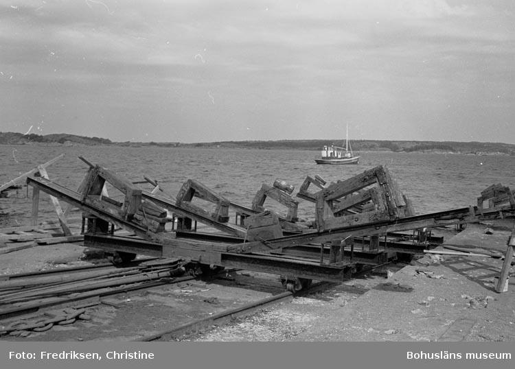 """Motivbeskrivning: """"19800520. Myrens Mekaniska Verkstad, Strömstad. Slipvagnarna tas upp efter sjösättning. I bakgrunden """"Ford"""". N."""""""