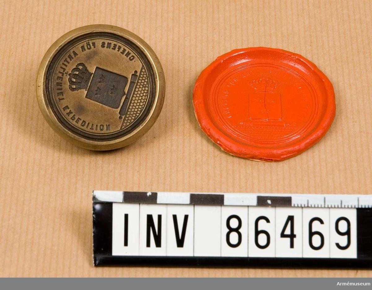 Grupp M V. En räfflad sköld med Sveriges tre kronor; ovanpå skölden en kungl. krona; nedanför skölden en granat; nederst en mur, allt omgivet av tre släta koncentriska cirkelränder.  Med avtryck i rött lack.