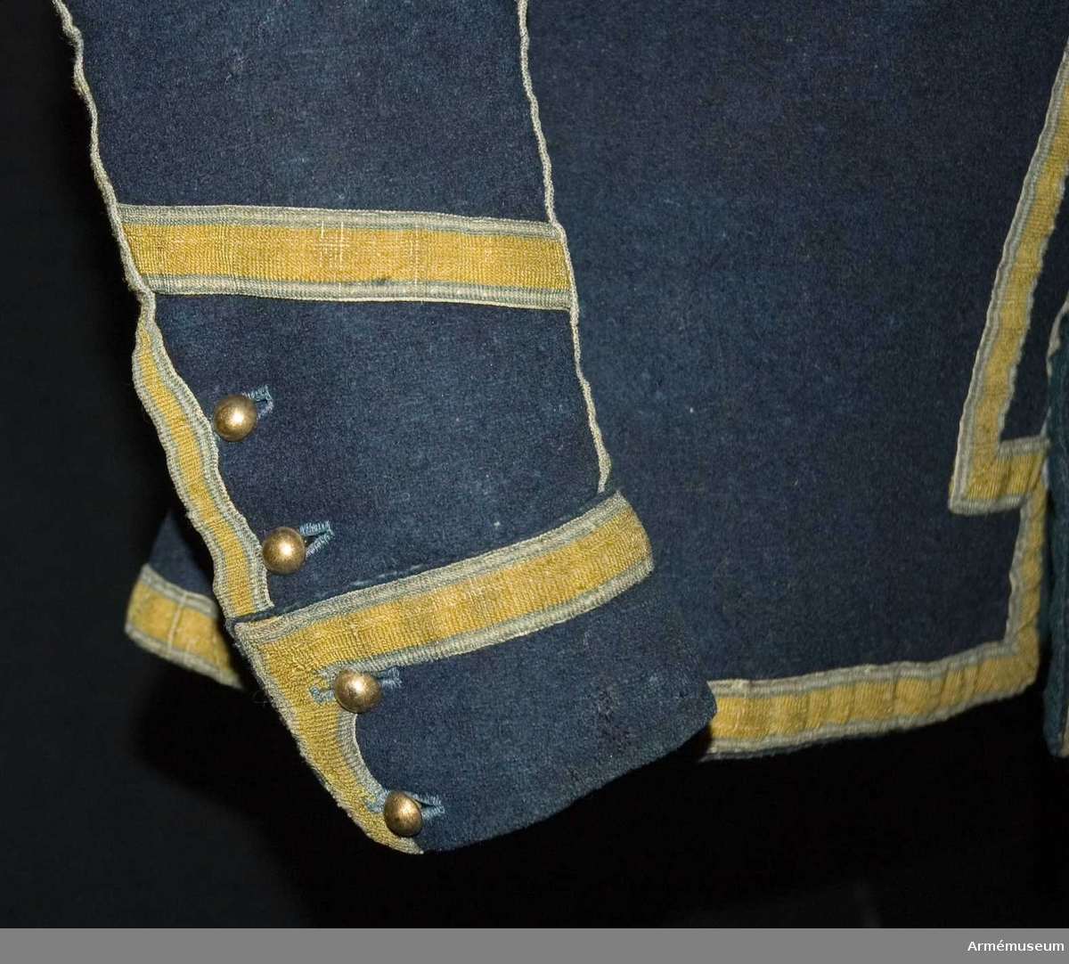 Grupp C:I. Jacka m/1779 av blått kläde med gula band. Banden har lin i varpen och lin samt ull i inslaget.