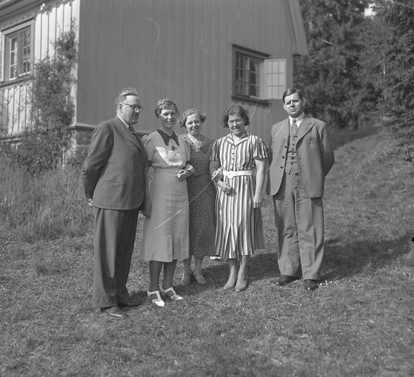 """Text till bilden:""""Gruppbild framför hus""""."""