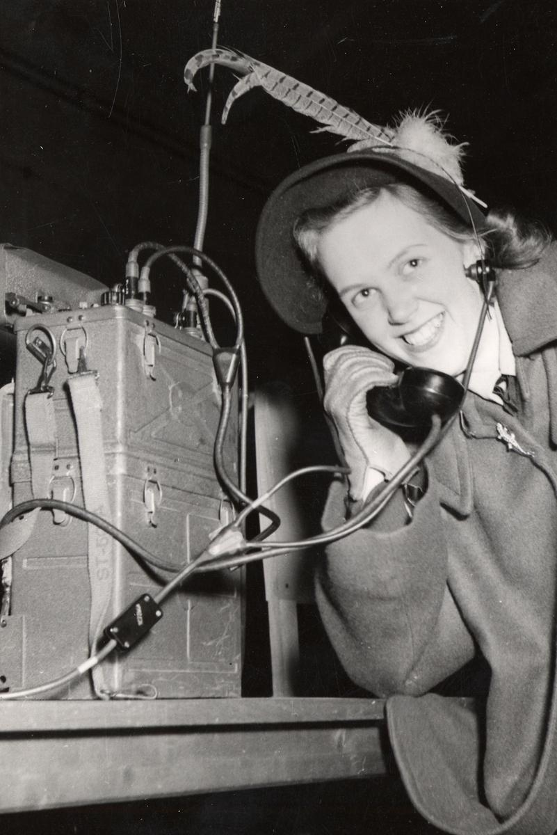 Kvinna lyfter på luren till fälttelefon under uppvisningsdag på Arméns underofficersskola (Försvarets läroverk) i Uppsala 1949.