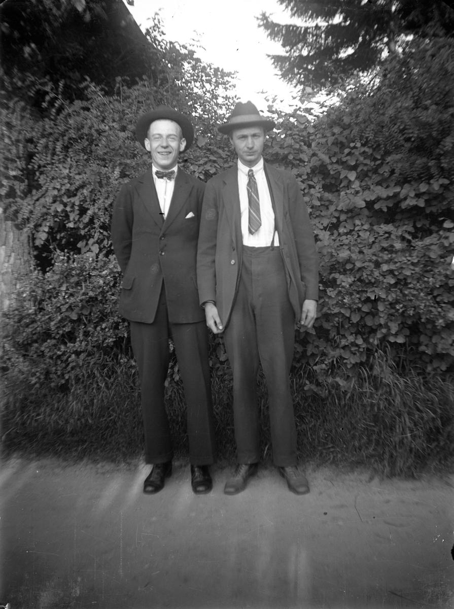Två män står framför ett buskage, Gustav Andersson till höger.