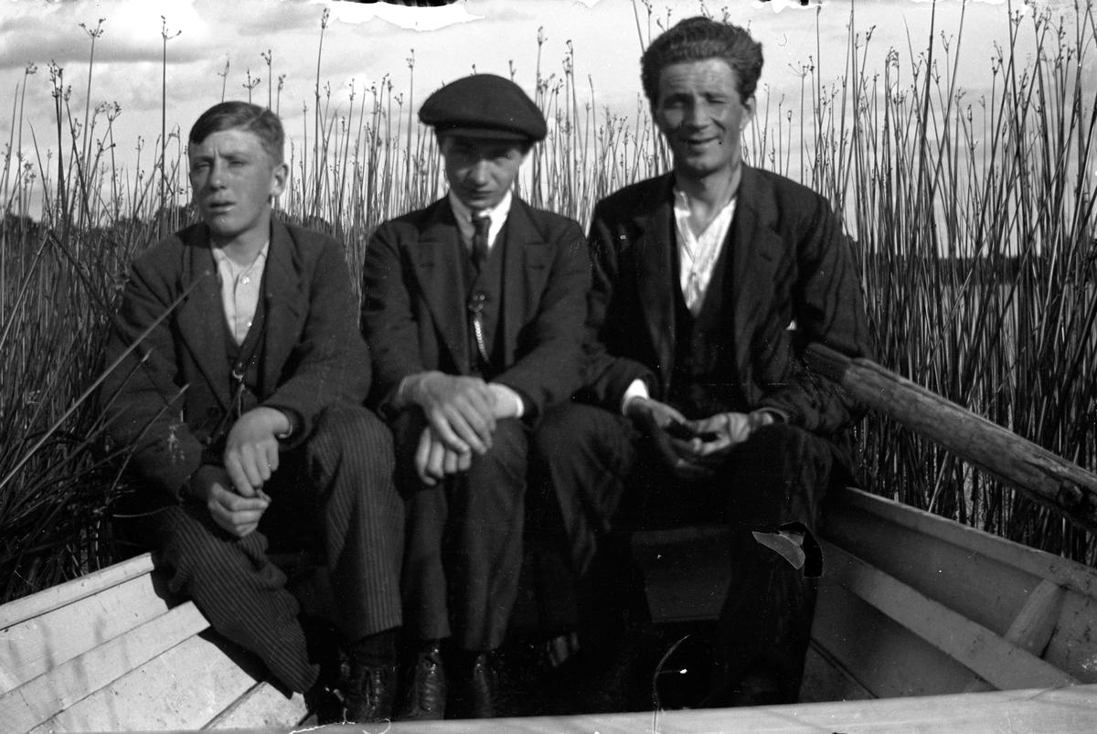 Tre män, Gustav Andersson i mitten, sitter i en roddbåt omgiven av vass.  Lungkliniken, Eksjö.