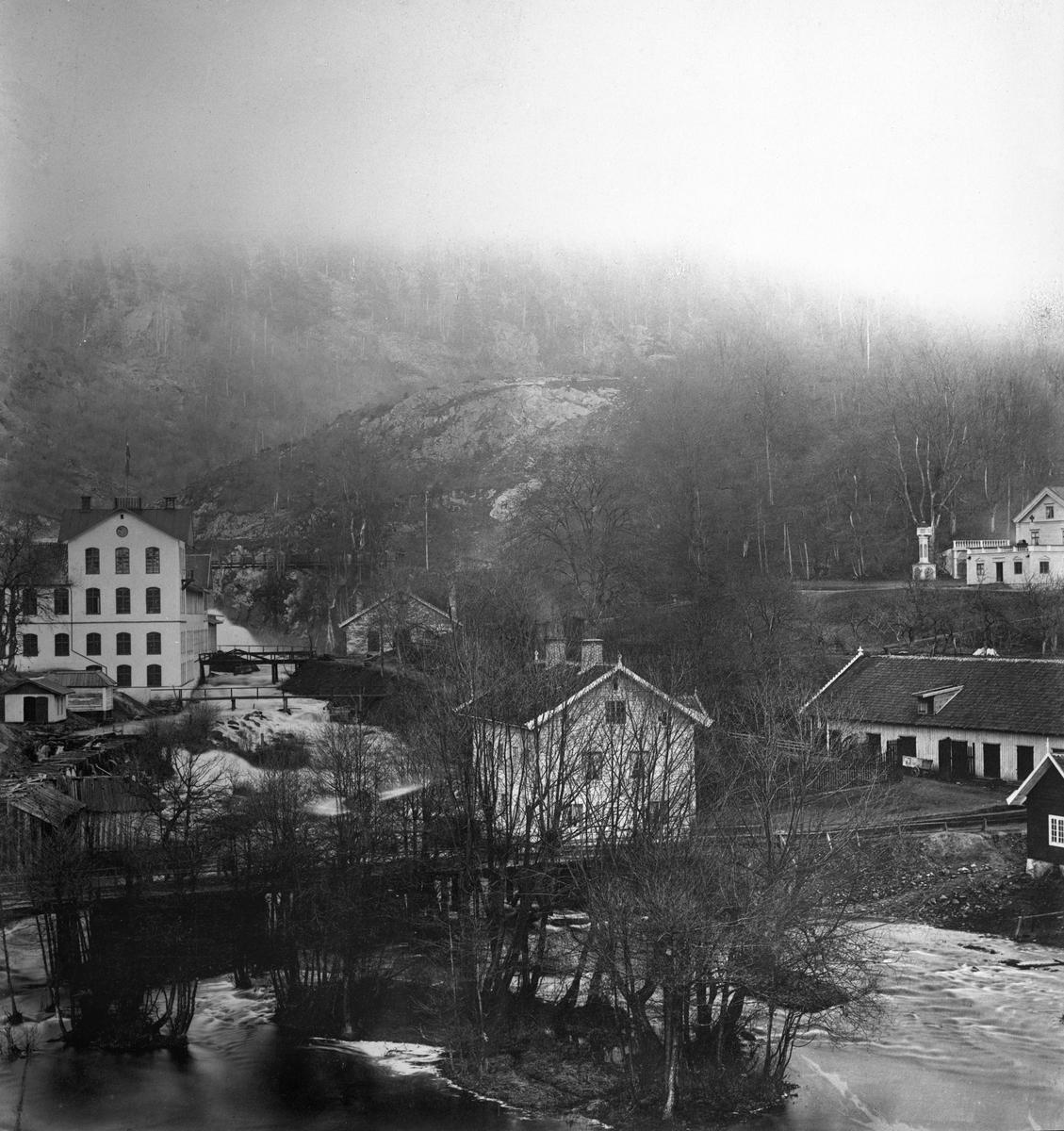 Vid stora fallen i Huskvarna ligger, uppe till vänster, byggnaden som idag är Husqvarna Fabriksmuseum sedan 27 april 1993, och inryms i det hus som fram till 1940-talet var vapenverkstad. Till vänster syns en del av Slottsvillan. I förgrunden går Hakarpsvägen med bro över vattnet. Bilden är från 1870-talet.