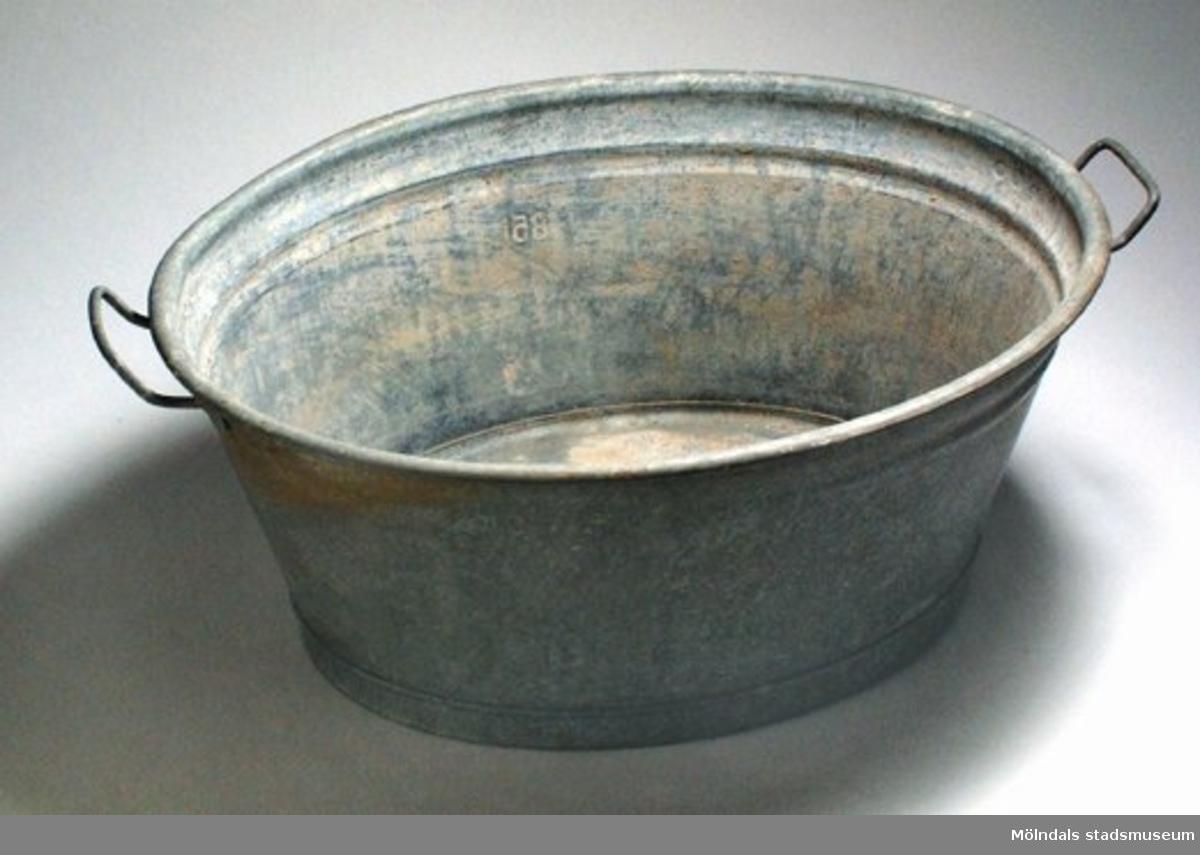 Oval plåtbalja (zinkplåt?) med två pånitade öron. Märken instansade i plåten - svårlästa: SULO 95 (?) 85 L. Det har varit cement/betong i baljan vilket sitter kvar på insidan.