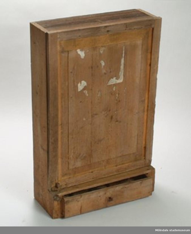 Skåp med två hyllor, dörr och låda under. Har ingått i utrustningen i snickarverkstaden.