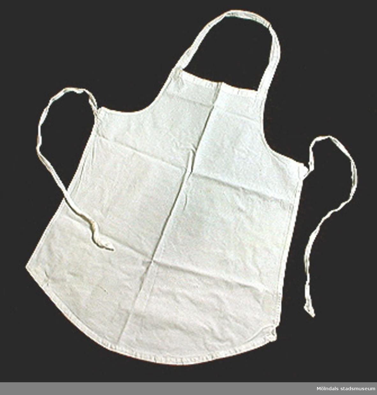Två vita skyddsförkläden för köksarbete.:1 Ett litet förkläde med hals- och midjeband. L 630, B 540.:2 Ett midjekort förkläde med midjeband. Kraftigt tyg. L 580, B 760.Från Stretereds centralkök genom husmor Elsa Blomstrand.